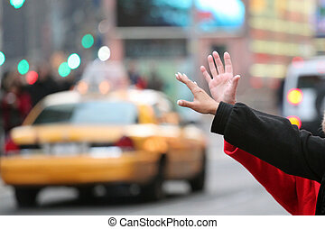 hands waving for a cab taxi in new york on times square