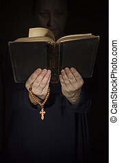 Hands with a bible and a cross