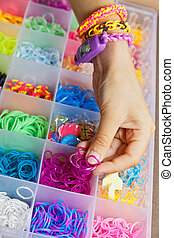 Hands with a bracelet and a set of rubber bands to weave