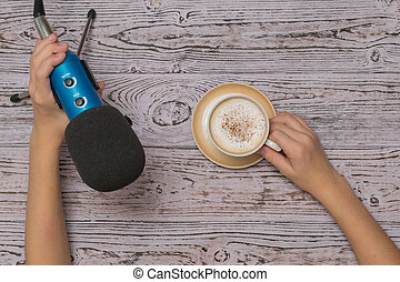 Hands with a Cup of coffee and a blue microphone on a wooden table. The process of creating music. The view from the top.