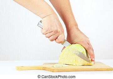 Hands with a knife shred cabbage on a wooden cutting board