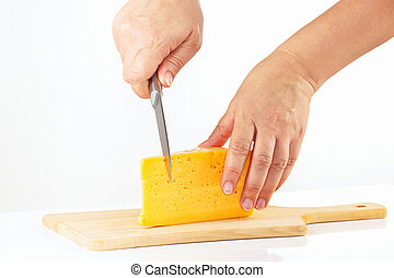 Hands with a knife sliced cheese on a wooden cutting board...
