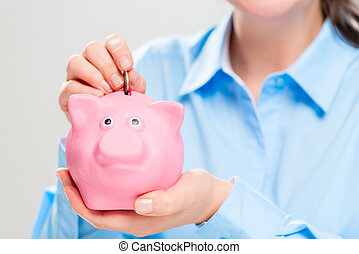 Hands with a pink piggy bank close-up - the concept of money accumulation