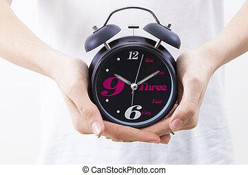 hands with alarm clock