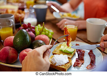 hands with bacon on fork at table full of food