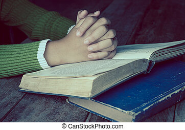 Hands with Bible on wood table