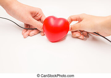 Hands with charging cables to help recovering heart on white background. Heart disease protection, proactive checkup, diagnosis, sickness prevention, healthcare examination tool concept.