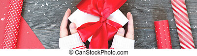 Hands with Christmas gift box and red wrapping paper banner