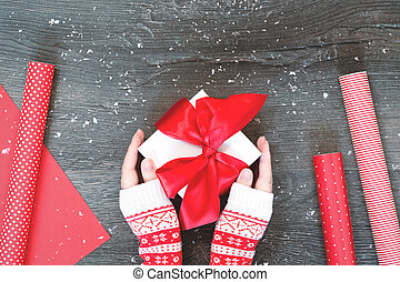 Hands with Christmas gift box and red wrapping paper