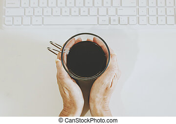 hands with coffee cup on desk