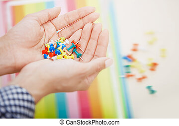 Hands with colorful pushpins