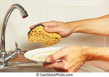 Hands with dirty dishes over the sink in kitchen