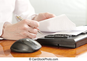 Hands with document on a computer keyboard