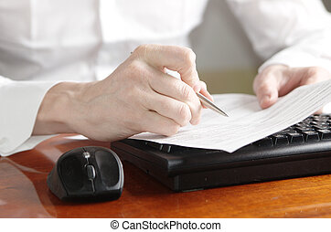 Hands with document on computer keyboard