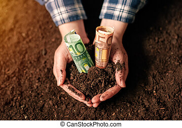 Hands with fertile soil and euro money banknotes