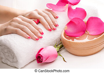 hands with fragrant rose petals and towel. Spa - hands with...