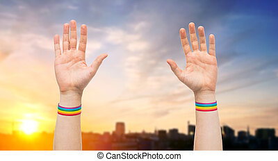 hands with gay pride rainbow wristbands