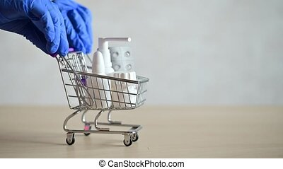 Hands with gloves carry a mini shopping cart full of medicine on the table. Medicine nasal spray and a tablet in the trolley. Pharmaceuticals at the pharmacy