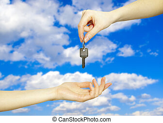 key  - Hands with key on a background sky