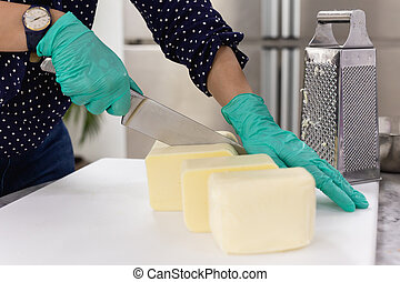 Hands with knife cutting a cheese on the white board.