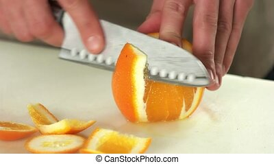 Hands with knife peeling fruit.