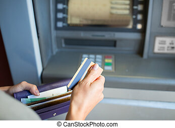 hands with money and credit card at atm machine - finance,...