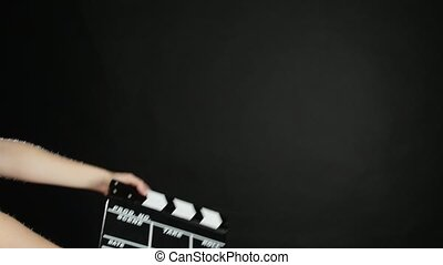 Hands with movie production clapper board, on black, slow...