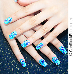 Hands with nail art on spotted background.
