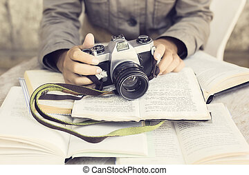 Hands with old camera and several open books on a wooden table