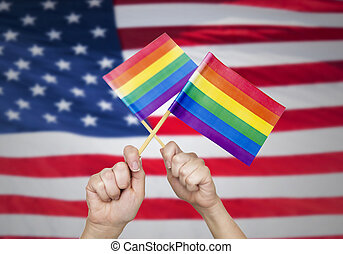 hands with rainbow flags over american background