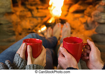 Hands with red coffee cups in front of lit fireplace -...