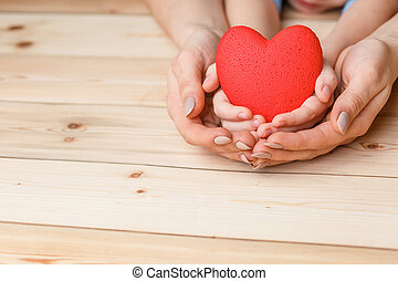hands with red heart on wooden background