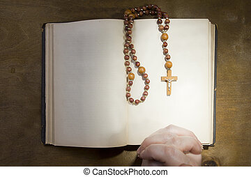 Hands with rosary and an old book