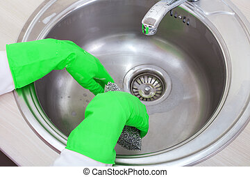 Hands with rubber gloves in the kitchen sink - Close up of...