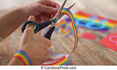 hands with scissors cut gay pride awareness ribbon -...