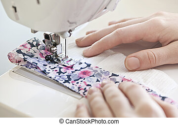 Hands with sewing machine