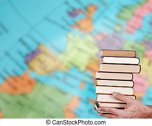hands with stacked books and geographic map