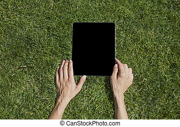 hands with tablet on grass