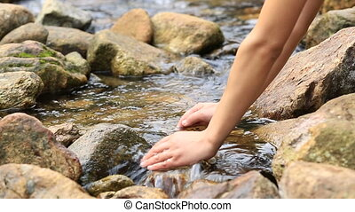 hands with the stream water - young woman hands with the...
