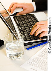 Hands working on a laptop typing a business document