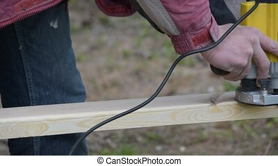 Hands working on a wooden plank with a plunge router - Hands...