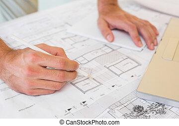 Hands working on blueprints