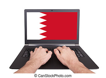 Hands working on laptop, Bahrain