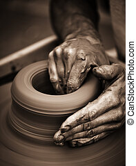 Hands working on pottery wheel , close up retro style toned...