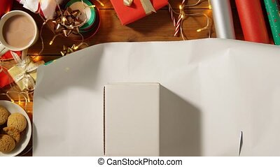 hands wrapping christmas gift into paper at home - holidays...