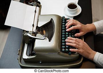 Hands writing on typewriter