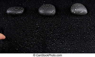 """Hands writing """"Welcome"""" word on a black background with drops of water"""