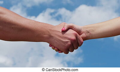 Handshake - A man and woman shaking hands on blue sky...
