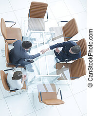 Handshake across the table. Meeting around a boardroom table.