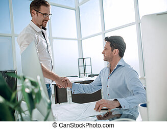 handshake between agent and customer in a modern office